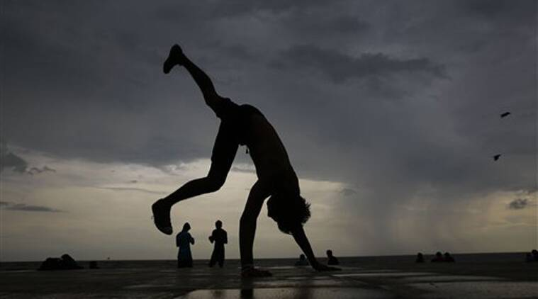 A boy practices somersault on the shore of the Arabian Sea during pre monsoon rains in Mumbai, India, Sunday, June 7, 2015. The monsoon rains have arrived in the southern most parts of the country. (AP Photo/Rafiq Maqbool)