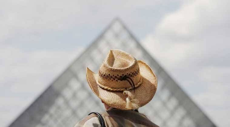 A tourist walks past the Pyramid at the Louvre museum in Paris (Source: Reuters)