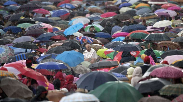 FILE - In this Wednesday, May 29, 2013 file photo, Pope Francis arrives for his weekly general audience in St. Peter's Square at the Vatican through a throng of people carrying umbrellas for the rain. Francis is issuing an encyclical on the environment and climate change by the end of June 2015 with an eye toward the end-of-year U.N. climate change conference in Paris. While previous popes have made strong moral and theological arguments in favor of environmental protection, Francis will be the first to address global warming in such a high-level teaching document. (AP Photo/Andrew Medichini)
