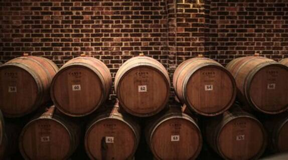 In this Wednesday, May 27, 2015 photo, oak barrels imported from France are stored in a barrel room, where produced wines are aged for at least 6 months, at the Gianaclis winery, one of Egypt's main wineries, in the Nile Delta, north of Cairo, Egypt. (AP Photo/Mosa'ab Elshamy)