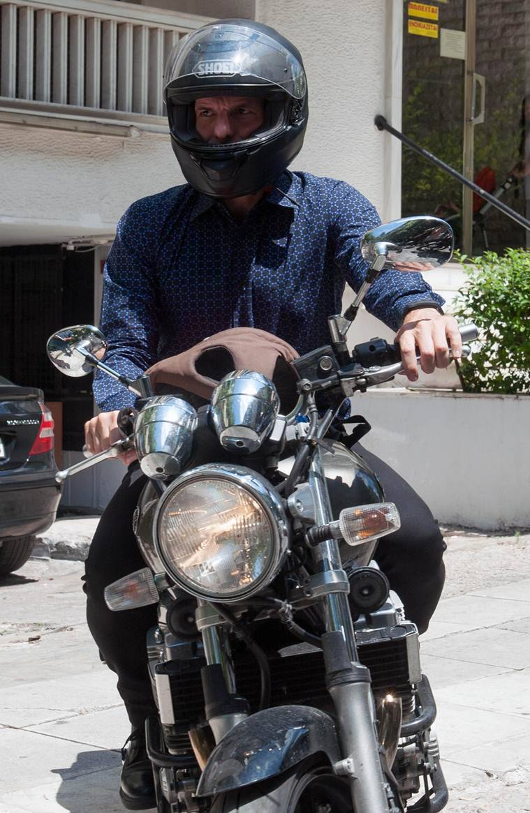 Yanis Varoufakis drives his motorcycle as he leaves from his house in Athens on July 6. (Source: AP)