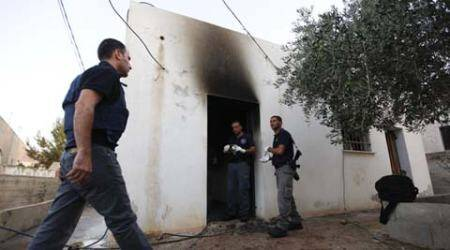 Israeli policemen inspect a house after it was torched in a suspected attack by Jewish settlers. AP