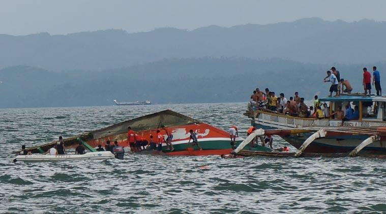 Rescuers help passengers from a capsized ferry boat, center, in Ormoc city on Leyte Island, Philippines, Thursday, July 2, 2015. A ferry capsized Thursday as it left a central Philippine port in choppy waters, leaving dozens dead and many others missing, coast guard officials said. (Ignatius Martin/Miquicar Photostudio via AP)