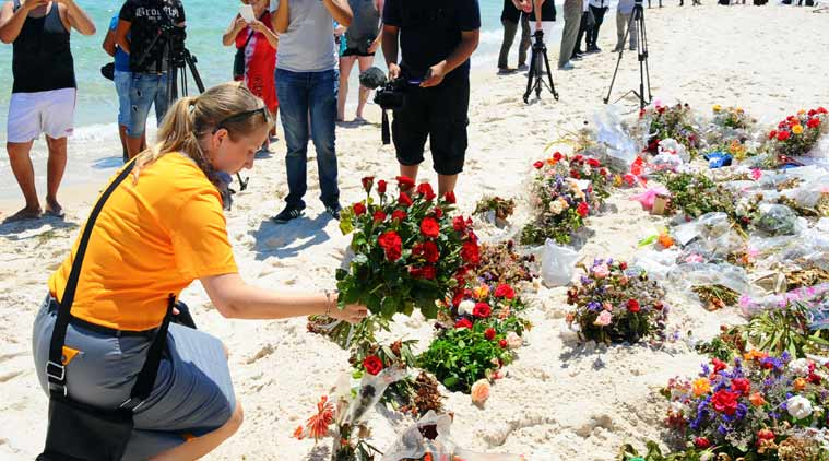 An unidentified tourist lays flowers to honor the victims of a deadly beach attack a week ago that killed 38 people, near the Imperial Marhaba hotel in the Mediterranean resort town of Sousse. (Source: AP photo)