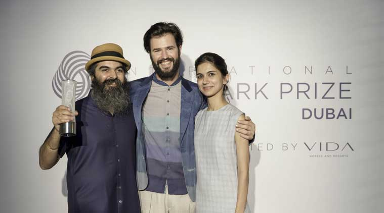 Suket Dhir and wife Svetlana pose with a model dressed in the winning garment