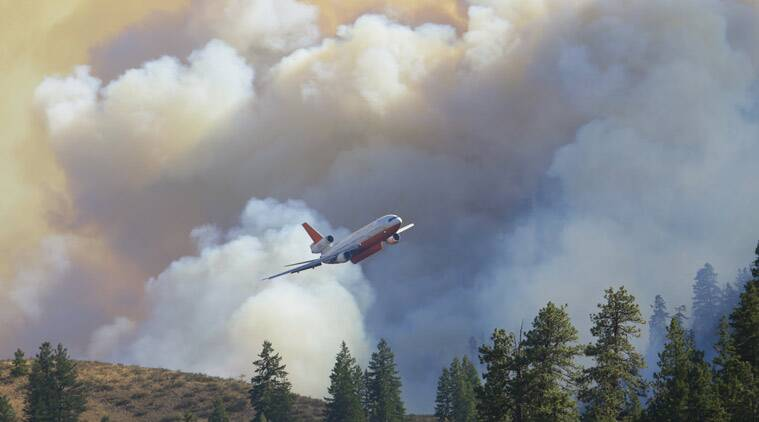 A tanker airplane tanker flies in front of billowing smoke after making a fire retardant drop on a wildfire north of Twisp, Washington. (Source: AP photo)