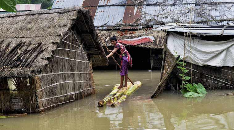 A woman crosses a flooded area over a raft made of banana tree trunks at Bura Bure in Morigaon district of Assam on Sunday. (PTI Photo)