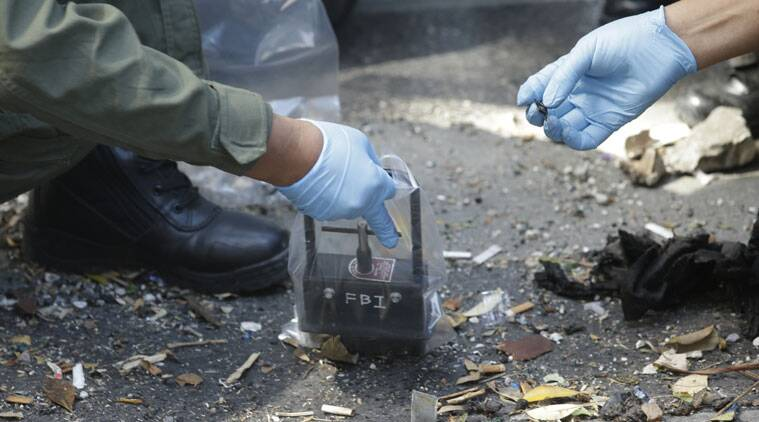 Police use a magnetic tool as they examine debris in front of the Erawan Shrine at Rajprasong intersection in Bangkok, Thailand, Tuesday, Aug. 18, 2015, as investigations continue the morning after an explosion. Police combed through shattered glass and other debris Tuesday from a bomb blast in central Bangkok, trying to determine who set off the most devastating single attack in the capital's recent history. (AP Photo/Sakchai Lalit)