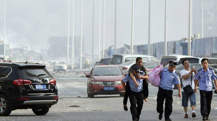 Chinese police help a man to safety near the site of an explosion in northeastern China's Tianjin municipality, Thursday, Aug. 13, 2015. Chinese state media reported huge explosions at the Tianjin port late Wednesday. (AP Photo/Ng Han Guan)