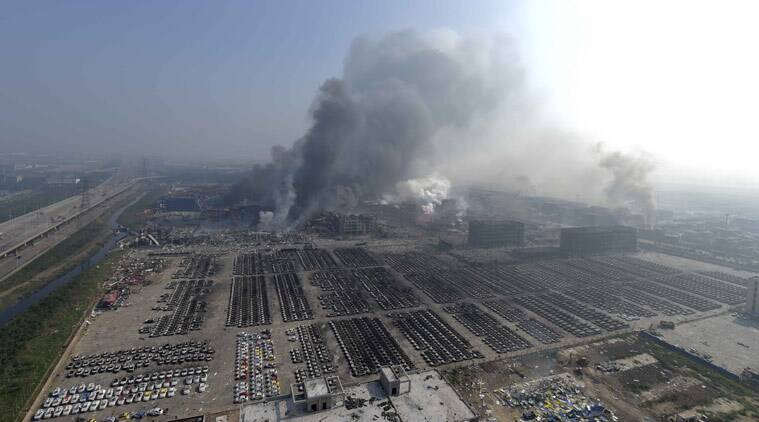 In this photo released by China's Xinhua News Agency, smoke rise from the site of explosions from a nearby building in the Binhai New Area in northeastern China's Tianjin municipality, Thursday, Aug. 13, 2015. Huge explosions in the warehouse district sent up massive fireballs that turned the night sky into day in the Chinese port city of Tianjin, officials and witnesses said Thursday. (Yue Yuewei/Xinhua via AP)