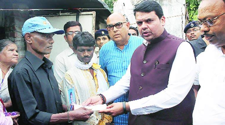 Chief Minister Devendra Fadnavis  presents a relief cheque to the family members of Muluk Meshram, who died in floods, in Nagpur on Sunday. PTI