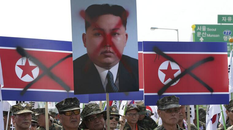 Members of the Korean Disabled Veterans Association by Agent Orange in Vietnam War, hold mock North Korean flags and a defaced image of North Korean leader Kim Jong Un during a rally denouncing North Korea in front of the Unification Bridge near the border village of Panmunjom in Paju, north of Seoul, South Korea, Thursday, Aug. 13, 2015. South Korea restarted propaganda broadcasts across the border with rival North Korea on Monday for the first time in 11 years in retaliation for the North allegedly planting land mines last week that maimed two South Korean soldiers. (AP Photo/Lee Jin-man)