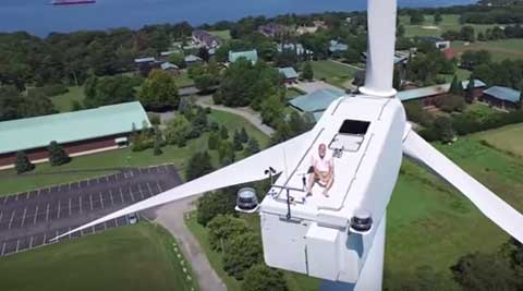 Drone captures monk relaxing atop wind turbine, 175 ft above theground