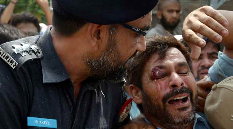 A Pakistani police officer comforts a man recovered from the rubble at the site of a suicide bombing in Shadi Khan, some 80 kilometers (50 miles) northwest from Pakistani capital, Sunday, Aug. 16, 2015. A pair of suicide bombers detonated their explosives at the home of an anti-Taliban provincial minister, killing him and more than a dozen others in eastern Pakistan, officials said. (Source: AP)