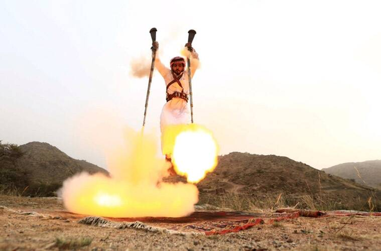 A man fires two weapons as he dances during a traditional excursion in Saudi Arabia. (Source: Reuters)