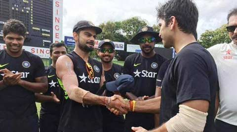 Captain duties: Virat Kohli hands Test cap to Naman Ojha