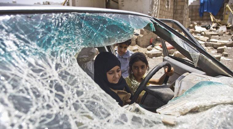 """FILE - In this May 18, 2015, file photo, Yemeni girls play with in a vehicle damaged by Saudi-led coalition airstrikes in Sanaa, Yemen. In a report released Tuesday, Aug. 18, Amnesty International says all sides fighting in Yemen have left a """"trail of civilian death and destruction"""" in the conflict, killing scores of innocent people in what could amount to war crimes. The latest report accused both the Saudi-led coalition carrying out airstrikes in Yemen and attacks by forces supporting and opposing the rebels, known as Houthis. (AP Photo/Hani Mohammed, File)"""