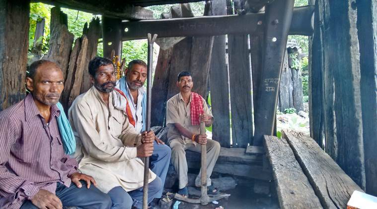 12 - trackmen sit inside a hut made of discarded wooden planks used for tracks.