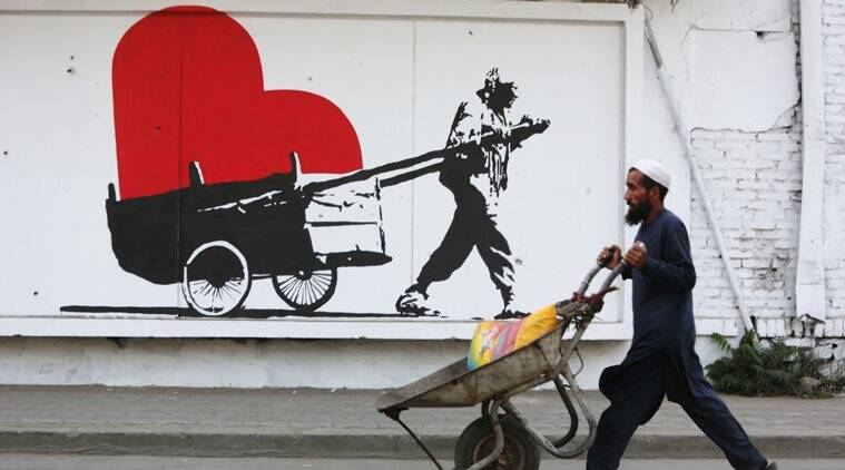 "In this Thursday, Aug. 20, 2015 photo, an Afghan laborer pushes his handcart in front of street art on a barrier wall of the NDS (National Directorate of Security) in Kabul, Afghanistan. ""I want people to define who really are the heroes of my city _ the people who clean the city, for instance,"" the 46-year-old artist Kabir Mokamel said. (AP Photo/Rahmat Gul)"
