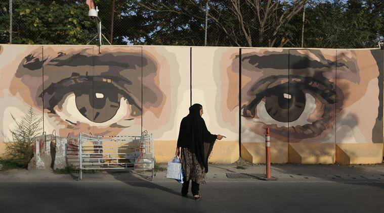 In this Thursday, Aug. 20, 2015 photo, an Afghan woman waits for transportation in front street art on a barrier wall of the NDS (National Directorate of Security) in Kabul, Afghanistan. he first installment of street art by a group called the Art Lords appeared in July, at the front entrance of the National Directorate of Security. A pair of beautiful, feminine eyes gazes out from the blast walls, a warning to corrupt officials. (AP Photo/Rahmat Gul)