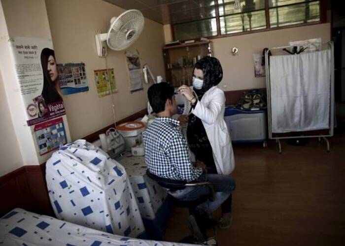 A plastic surgeon under the supervision of Afghan plastic surgeon Abdul Ghafar Ghayur, (unseen) removes facial hair from a patient's face at Aria City Hospital, in Kabul, Afghanistan (Source: Reuters)