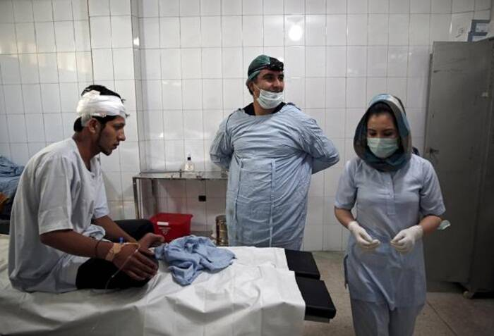 Plastic surgeon Abdul Ghafar Ghayur (C) speaks to a nurse after an operation at Aria City Hospital, in Kabul, Afghanistan (Source: Reuters)