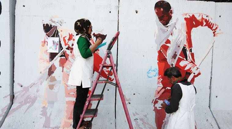 In this Thursday, Aug. 20, 2015 photo, independent Afghan artists paint on a barrier wall which blocks a main gate of the presidential palace in Kabul, Afghanistan. (AP Photo/Rahmat Gul)
