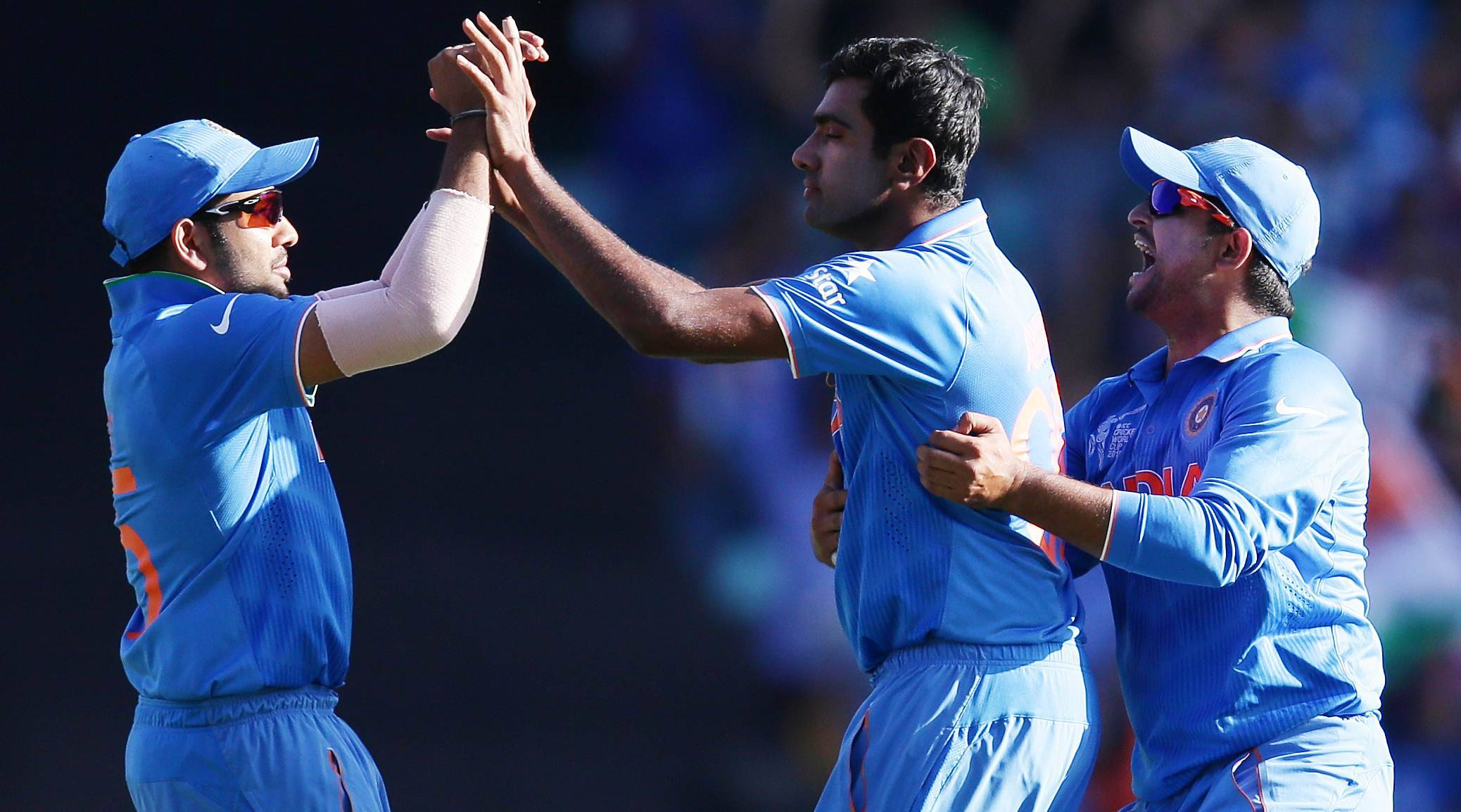 India's Ravichandran Ashwin, centre, is congratulated by teammates Rohit Sharma and Suresh Raina, right, after taking the wicket of Australia's Glenn Maxwell  during their Cricket World Cup semifinal in Sydney, Australia, Thursday, March 26, 2015. (AP Photo/Rob Griffith)