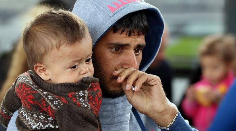 A man holds a child as migrants arrive at the Westbahnhof station in Vienna, Austria, Sunday, Sept. 6, 2015. Since Saturday more than 7,000 Arab and Asian asylum seekers surged across Hungary's western border into Austria and Germany following the latest erratic policy turn by Hungary's immigrant-averse government. (AP Photo/Ronald Zak)