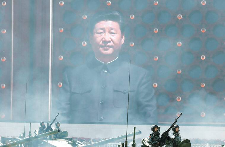 A giant image of President Xi Jinping looms on a TV screen as a column of China's most advanced tanks passes by during the parade in Beijing on Thursday. (Source: AP photo)