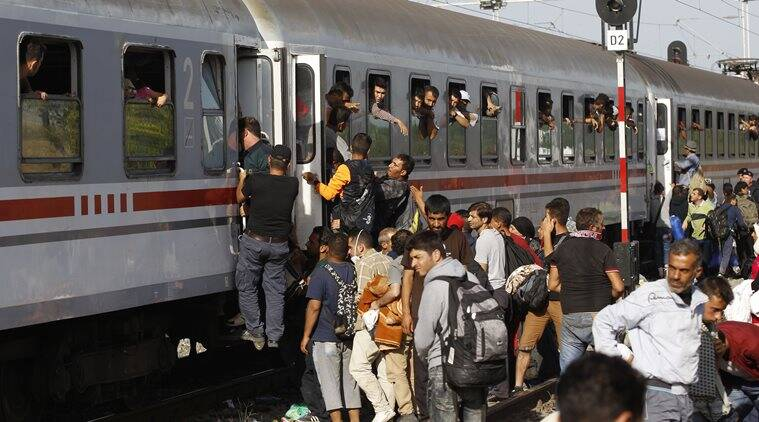 Migrants try to board a train in Tovarnik, Croatia, Friday, Sept. 18, 2015. The train with eleven carriages left Friday morning carrying hundreds to refugee centers in the capital Zagreb and elsewhere. (AP Photo/Petr David Josek)