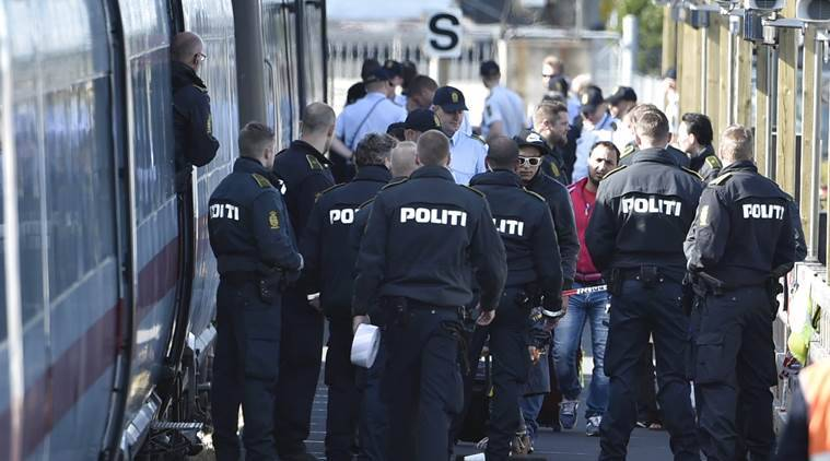 Danish police guard a train carrying migrants, mainly from Syria and Iraq, at Rodby train station, south of Denmark, September 9, 2015. The migrants, hoping to get to Sweden, arrived at Rodby on Tuesday night and refused to leave the train to get registered in Denmark.  REUTERS/Jens Norgaard Larsen/Scanpix Denmark    ATTENTION EDITORS - THIS IMAGE WAS PROVIDED BY A THIRD PARTY. FOR EDITORIAL USE ONLY. NOT FOR SALE FOR MARKETING OR ADVERTISING CAMPAIGNS. THIS PICTURE IS DISTRIBUTED EXACTLY AS RECEIVED BY REUTERS, AS A SERVICE TO CLIENTS. DENMARK OUT. NO COMMERCIAL OR EDITORIAL SALES IN DENMARK. NO COMMERCIAL SALES.