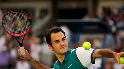 Roger Federer, of Switzerland, hits balls into the stands after defeating Philipp Kohlschreiber, of Germany, during the third round of the U.S. Open tennis tournament, Saturday, Sept. 5, 2015, in New York. (AP Photo/Charles Krupa)