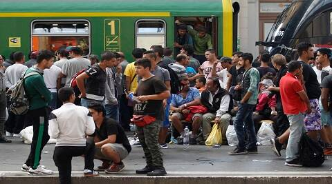Migrants wait  at the Keleti Railway Station in Budapest, Hungary, Thursday, Sept. 3, 2015. Migrants are now allowed to enter the station but direct trains from Budapest to Western Europe are currently out of operation until further notice. (Zsolt Szigetvary/MTI via AP)