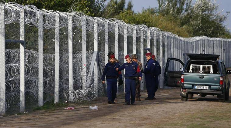 Hungarian police officers check a hole at the fence where migrants tried to cross the border line between Serbia and Hungary in Roszke, southern Hungary, Tuesday, Sept. 15, 2015.