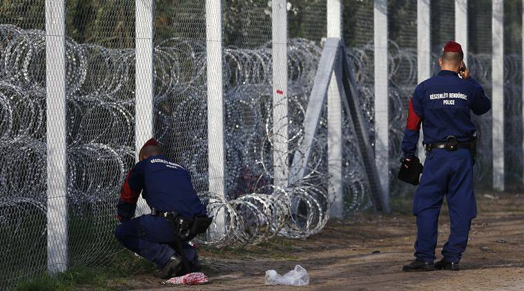 Hungarian police officers repair a hole at the fence where migrants tried to cross the border line between Serbia and Hungary in Roszke, southern Hungary, Tuesday, Sept. 15, 2015. Hungary is set to introduce much harsher border controls at midnight — laws that would send smugglers to prison and deport migrants who cut under Hungary's new razor-wire border fence. The country's leader was emphatically clear that they were designed to keep the migrants out. (AP Photo/Matthias Schrader)