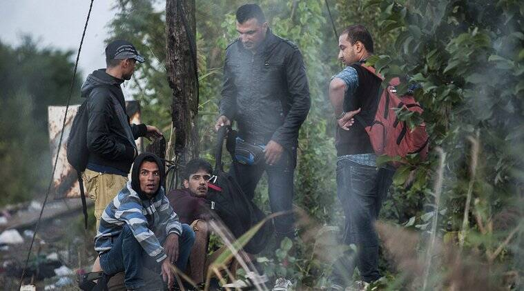 Migrants wait on the Serbian side of the border between Hungary and Serbia near Roszke, 180 kms southeast from Budapest, Hungary, Tuesday, Sept. 15, 2015. (Sandor Ujvari/MTI via AP)