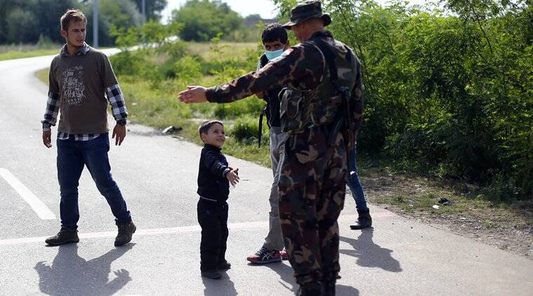 A young migrant boy goes to shake hands with a Hungarian soldier at the border between Serbia and Hungary in Asotthalom near Roszke, southern Hungary, Tuesday, Sept. 15, 2015. Hungary has declared a state of emergency in two of its southern counties bordering Serbia because of the migration crisis, giving special powers to police and other authorities. (AP Photo/Matthias Schrader)
