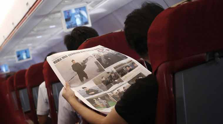A woman reads a newspaper displaying a series of photos of North Korean leader Kim Jong Un aboard an Air Koryo flight from Pyongyang, North Korea, bound for Beijing. AP Photo