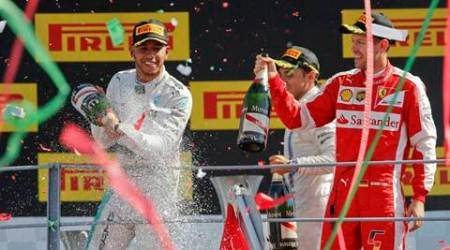 Monza  :  Mercedes driver Lewis Hamilton, left, winner, sprays champagne on the podium flanked by second placed Ferrari driver Sebastian Vettel, of Germany, and third placed Felipe Massa, of Brazil, during the podium ceremony for the Formula One Italian Grand Prix, at the Monza racetrack, Italy, Sunday, Sept. 6, 2015. AP/PTI(AP9_6_2015_000186A)