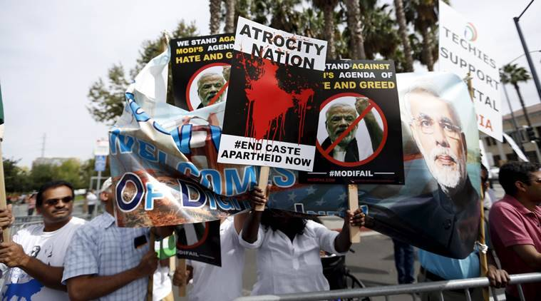 Demonstrators hold signs in protest against Indian Prime Minister Narendra Modi before a community receptiion outside SAP Center in San Jose, California September 27, 2015. REUTERS/Stephen Lam
