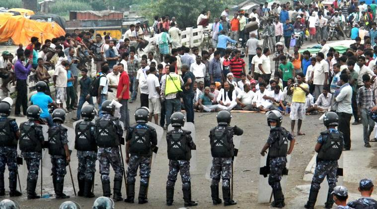 Nepalese policemen face protestors belonging to ethnic and religious groups dissatisfied with Nepal's new constitution adopted on Sunday, in Birgunj, a town bordering India in Nepal, Thursday, Sept. 24, 2015. Nepal's top political parties on Thursday reached out to protesters angry about the country's new constitution, after violence in the region bordering India halted more than 1,000 oil tankers and trucks with essential supplies from entering Nepal. (AP Photo/Ram Sarraf)