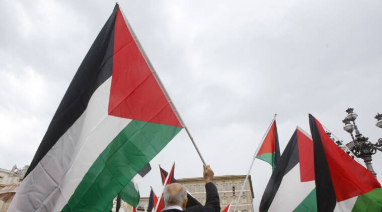 FILE- In this Aug. 3, 2014 file photo, activists wave Palestinian flags as Pope Francis celebrates the Angelus noon prayer from his studio window overlooking St. Peter's square at the Vatican. On Thursday, Sept. 10, 2015, the U.N. General Assembly overwhelmingly approved a resolution allowing the Palestinians and the Holy See to raise their flags at U.N. headquarters, a symbolic step pursued by the Palestinians in their quest for an independent state. (AP Photo/Riccardo De Luca)