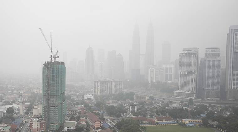 Malaysia's landmark building Petronas Twin Towers, center, and other buildings are shrouded by haze in Kuala Lumpur, Malaysia on Tuesday, Sept. 15, 2015. A layer of heavy haze has forced Malaysian authorities to shut schools in four states, including Kuala Lumpur, with officials to begin cloud seeding operations to try to induce rain to help clear the air. (AP Photo/Joshua Paul)