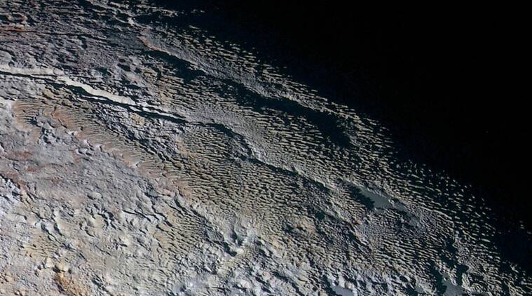 In this extended color image of Pluto taken by NASA's New Horizons spacecraft, rounded and bizarrely textured mountains, informally named the Tartarus Dorsa, rise up along Pluto's day-night terminator and show intricate but puzzling patterns of blue-gray ridges and reddish material in between. (Credits: NASA/JHUAPL/SWRI)