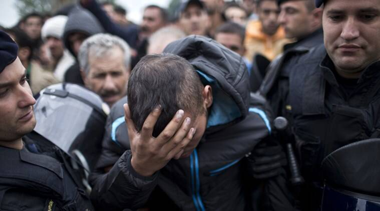 Croatian police officers support an injured man in front of a reception center in Opatovac, Croatia, Tuesday, Sept. 22, 2015. Scuffles have broken out between Croatian police and asylum-seekers after they were barred from entering a newly opened reception center meant to register those seeking sanctuary in Europe. (AP Photo/Marko Drobnjakovic)