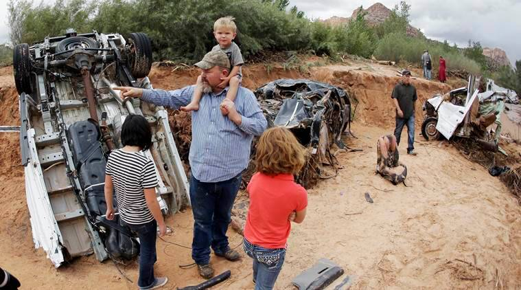 Russ Cook and his family stands next to severely damage vehicles swept away during a flash flood Tuesday, Sept. 15, 2015, in Hildale, Utah. Water swept away the vehicles in the Utah-Arizona border town, killing several people. (AP Photo/Rick Bowmer)