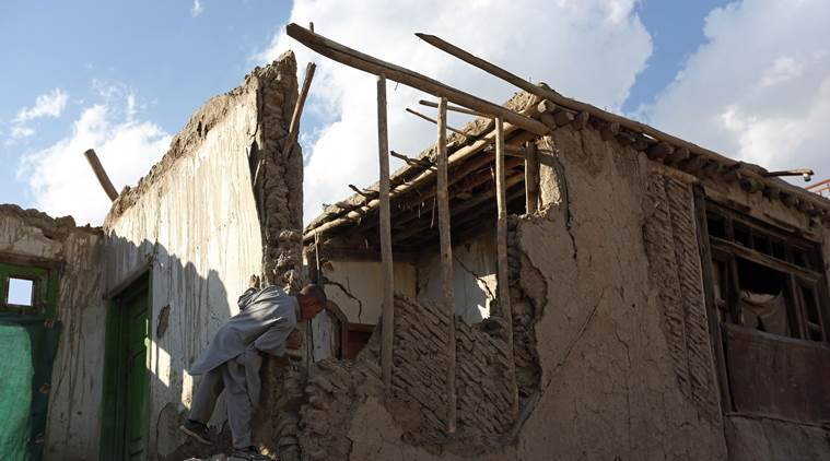 An Afghan boy looks at a damaged house following an earthquake, in Kabul, Afghanistan, Monday, Oct. 26, 2015. (AP Photo)