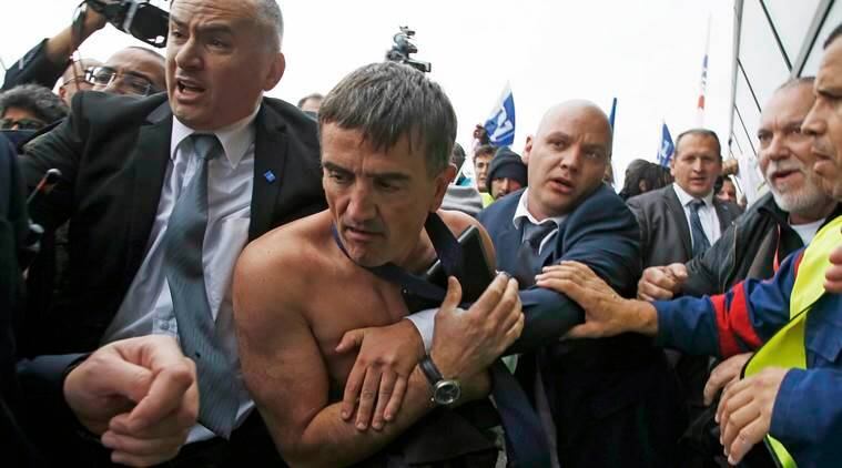A shirtless Xavier Broseta (2ndL), Executive Vice President for Human Resources and Labour Relations at Air France, is evacuated by security after employees interrupted a meeting with representatives staff at the Air France headquarters building at the Charles de Gaulle International Airport in Roissy, near Paris, France, October 5, 2015. Air France confirmed in a meeting with staff on Monday that it plans to cut 2,900 jobs by 2017 and shed 14 aircraft from its long-haul fleet as part of efforts to lower costs, two union sources said. REUTERS/Jacky Naegelen TPX IMAGES OF THE DAY