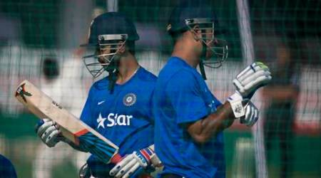 Indian cricket captain Mahendra Singh Dhoni, right, walks past teammate Ajinkya Rahane during a practice session in Kanpur, India, Saturday, Oct. 10, 2015. India will play South Africa in the first of their five one-day match series on Sunday.  (AP Photo/Saurabh Das)